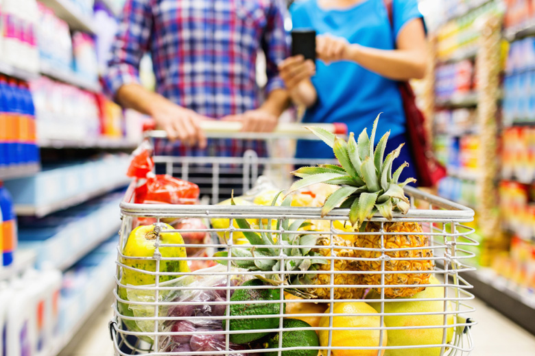 Fruits In Cart With Couple Using Smart Phone At Store